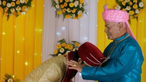 Young Indian man taking blessings from his father on his marriage day