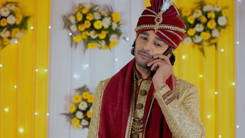 An attractive Indian groom talking on a smartphone - Indian wedding