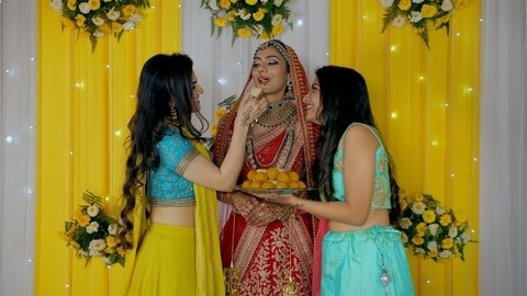 Attractive relatives/friends feeding a Punjabi bride some Indian sweets on stage