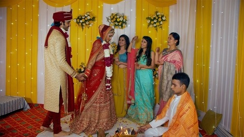 Indian bride and groom taking Pheras around the sacred fire while priest performing wedding rituals
