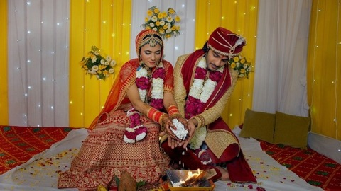 Punjabi bride and groom throwing rice flakes in the holy fire during Indian marriage rituals