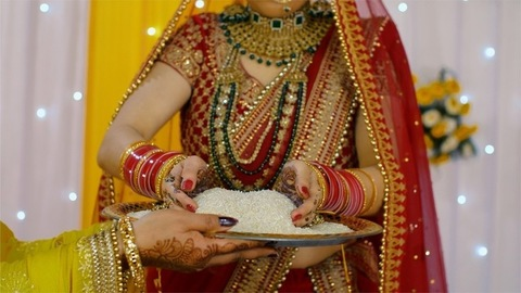 Hands of an Indian bride picking up a handful of puffed rice for Vidai ceremony