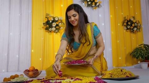 Beautiful Indian female making a floral rangoli design on the festival of Diwali