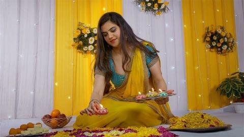 Beautiful Indian female decorating floral rangoli with burning Diyas on Diwali