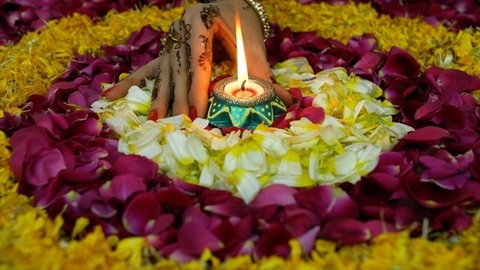 Closeup shot - Henna mehndi/tattoo on woman hand doing Diwali decorations