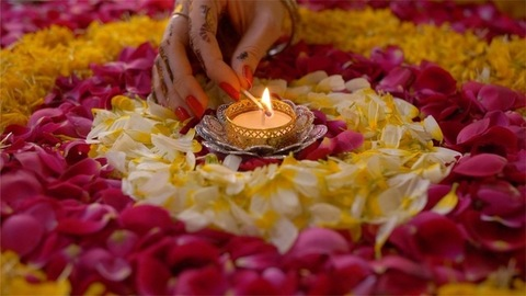 Closeup shot of an Indian female's hand decorating floral rangoli with a Diya