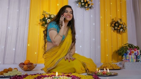 A beautiful young woman wishing her friends Happy Diwali over a phone call