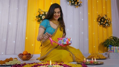 Pretty Indian female excitedly opening her Diwali gifts in traditional clothing