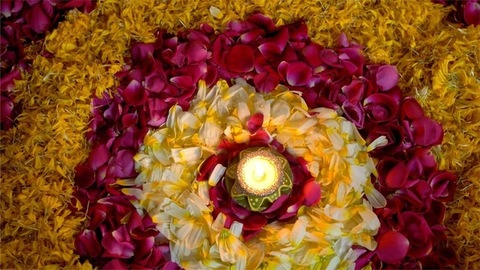 Top view shot of a glowing wax lamp decorated on floral rangoli - Diwali festival