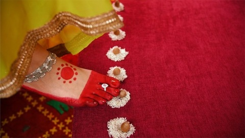 Closeup shot of an Indian bride's feet touching betel nut during a wedding ritual