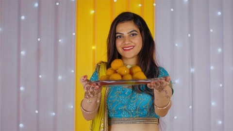 Pretty Indian woman smiling and showing sweets to the camera - Diwali festival