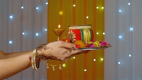 Closeup shot of mehndi on Indian woman hands holding a decorated puja thali