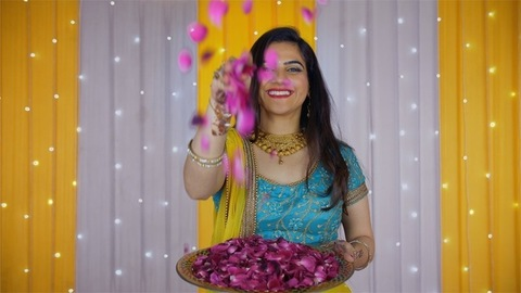 Pretty Indian girl happily throwing rose petals while looking towards the camera