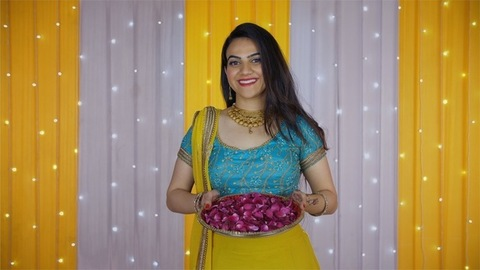 Traditional Indian woman throws a plateful of rose petals towards the camera