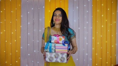 Attractive young girl carrying a heap of Diwali presents in traditional lehenga