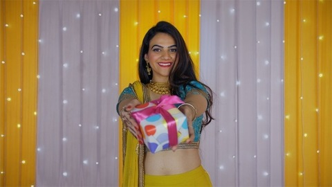 Beautiful young female smiling and offering Diwali's special gift to the camera
