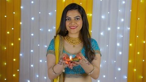 Bokeh shot - A beautiful young female holding a burning Diya on Diwali festival