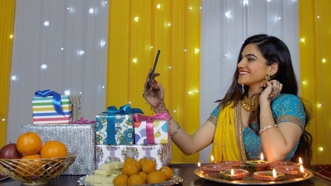 Pretty Indian girl happily posing while capturing selfies during the festive season