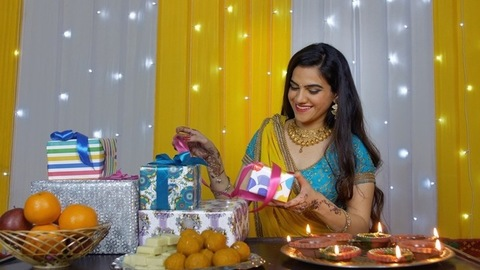 Medium shot - Young woman happily opening her Diwali gifts in traditional wear