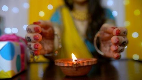 Henna mehndi/tattoo on woman hands protecting oil lamp/lantern with bokeh effect