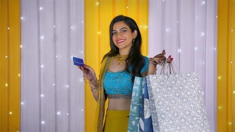 Beautiful young female showing her credit card and shopping bags while smiling