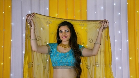 Medium shot of an attractive Indian female smiling after lifting her veil off