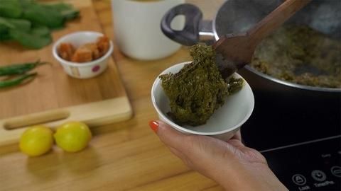 Indian female serving delicious Punjabi cuisine Sarson ka saag in a white bowl
