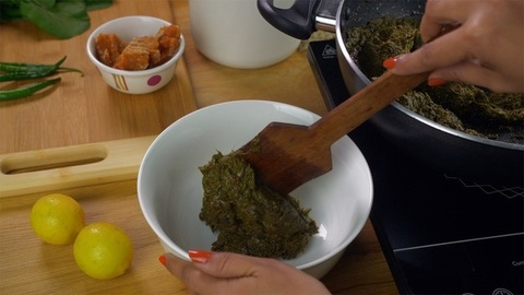 Closeup shot of woman hands pouring freshly cooked saag in a ceramic bowl
