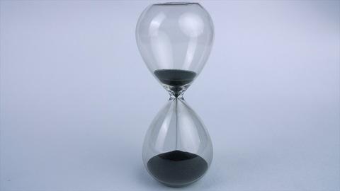 Closeup shot of a modern transparent hourglass flowing black sand - time concept