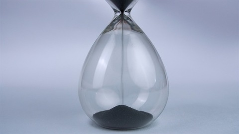Extreme close up of a transparent hourglass with flowing black sand - time concept