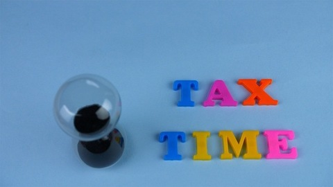 """A sand clock flowing next to the """"Tax Time"""" words composed with plastic letters"""