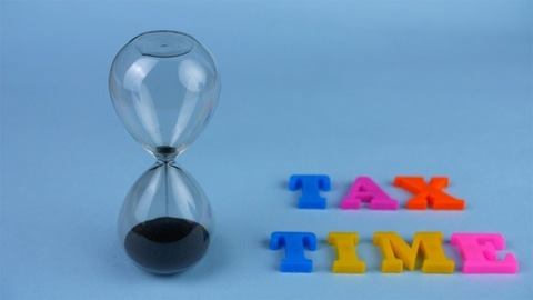 """Closeup shot of a sand clock and """"Tax Time"""" words composed with plastic letters"""