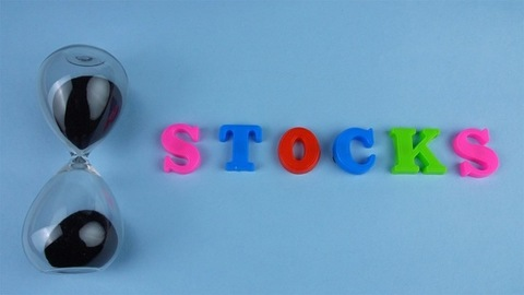 """Tilt shot of the word """"Stocks"""" composed with colorful letters on a blue platform"""