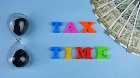 """Top view shot of """"Tax Time"""" words beautifully arranged on the blue platform"""
