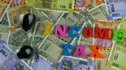 """Top view shot of colorful letters spelling the words """"Income Tax"""" - finance concept"""