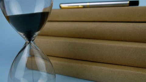 Closeup shot of sand running through an hourglass next to a stack of books