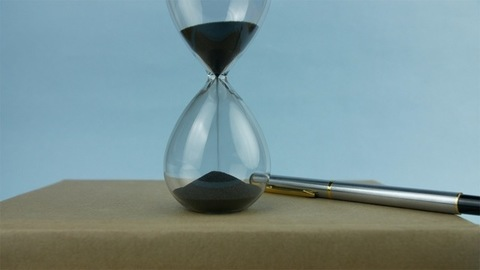 Closeup shot of sand running through an hourglass with a pile of books and a pen