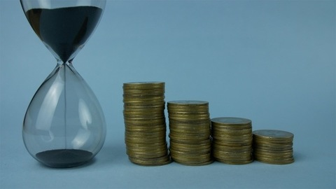 Time is money concept - Closeup shot of an hourglass with Indian coin currency