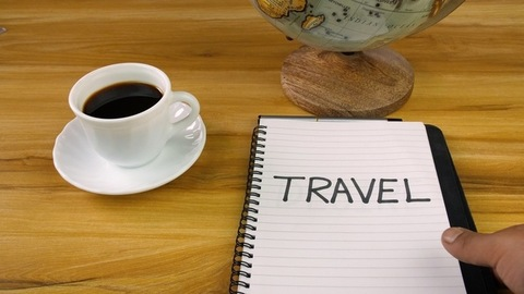 """Closeup of shot male's hand placing a diary with """"Travel"""" word on a wooden table"""