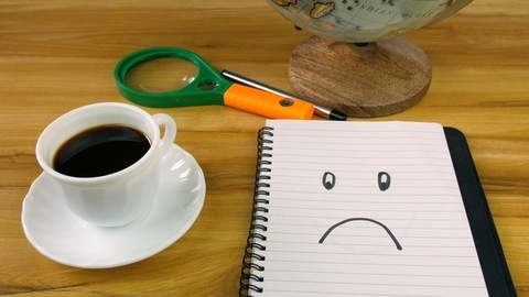 Closeup of male's hand placing a diary with sad face emoticon on a wooden table