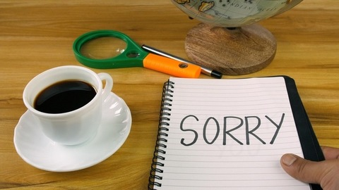 """Closeup shot of male's hand placing a diary with """"Sorry"""" word on a wooden table"""