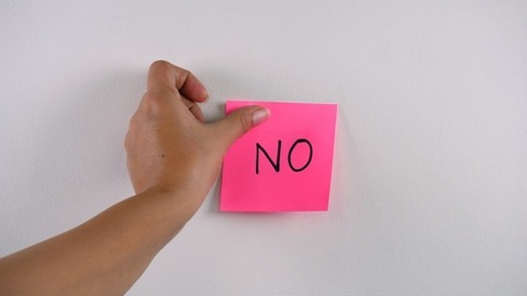 """Closeup shot of woman's hand sticking note with """"NO"""" word on a white background"""