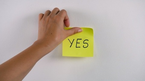 """Closeup shot of woman's hand sticking note with """"YES"""" word on a white background"""