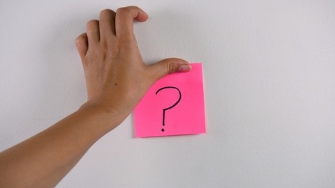 Woman's hand sticking note with a question mark symbol on a white wall/surface
