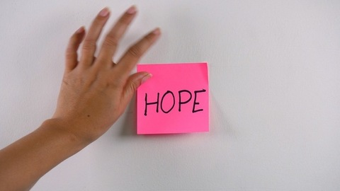 """Closeup shot of woman's hand sticking note with """"Hope"""" text on a white wall"""