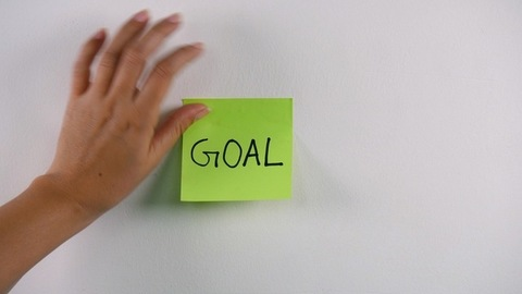 """Indian woman's hand sticking note with """"Goal"""" text on the white background"""