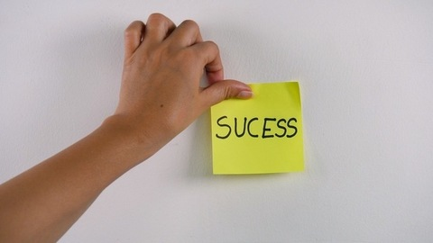 """Closeup shot of woman's hand sticking note with """"Success"""" text on a white wall"""