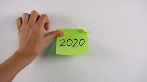 """Closeup shot of woman's hand sticking note with """"2020"""" text on a white wall"""