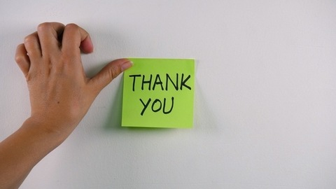"""Closeup shot of woman hands sticking note with """"Thank you"""" text on a white wall"""