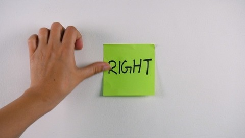 """Closeup shot of woman hands sticking note with """"Right"""" text on a white wall"""